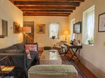 The living room is furnished with comfortable seating, soft lighting and a large rug.