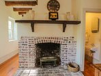 The fireplace, which is original to the 1820 home, and the half bathroom separate the dining & kitchen areas.