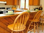 A breakfast bar in between the dining room and kitchen can comfortably seat 3 people.
