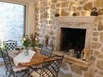 Rustic style veranda with stone walls, chimney and a dining table for 6