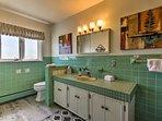 The en-suite bathroom has retro green tiles and glass walk-in shower.