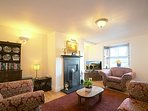 The stylish living room has original cast iron open fire, window shutters, LCD TV and DVD