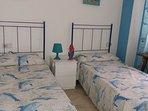 Dormitorio con 2 camas y armario empotrado.