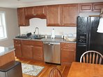 Kitchen has wood cabinets with granite counters.