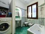 The green bathroom with bathtub and washing machine.