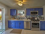 Cobalt blue cabinets and custom tiles highlight the kitchen area.