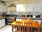 The kitchen is complete with appliances, cooking, and dining utensils