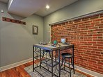 Enjoy cozy meals with travel companions around the table beside the brick wall.