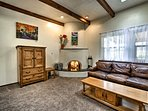 The living room boasts exposed vigas and a lovely wood-burning Kiva fireplace.