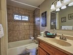 Freshen up in this full bathroom's shower/tub combo.