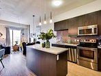 The kitchen has an electric range cooktop, oven, microwave, fridge/freezer.