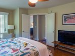 This guest bedroom has a queen size bed, an HDTV, and access to the screened porch.