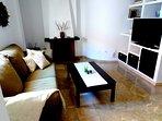 Väldigt vackert vardagsrum med bekväm soffa, TV och öppen spis.