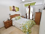 The en-suite double bedroom with aircon, double wardrobe, drawer unit, fan, doors to the back garden