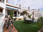 The villa with astro turfed front garden with outside dining (bikes not included in Rental)