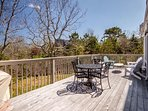 Deck off of sliding doors in living room looking over forested land