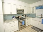 Stainless steel gas stove and microwave.  Granite Counter tops