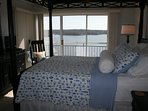Master bedroom with feather topper. Super comfy!. Patio door onto wrap around deck. Awesome view!