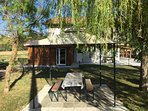 Giardino esterno con gazebo, panche e tavolo.