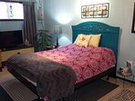 This fully furnished room has a queen sized bed.