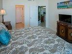 Master bedroom with flat screen TV looking towards kitchen