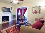 Living room with sofa sleeper, TV w/dish, hardwood floors.