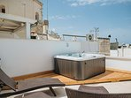 Roof terrace with Jacuzzi and sunbeds with view on Cathedral dome and sea water.