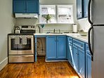 These blue cabinets are a perfect touch to this quaint, fully equipped kitchen.