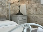 Peregrine, characterful luxury bedroom within the old cone with exposed stonework plus stone floor.