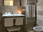 Gyr ensuite bathroom with feature rain shower, bidet,toilet, sink and radiator for cooler months.