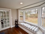 Window nook in the living room and entrance to sun room with additional dining
