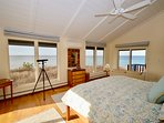 Master bedroom with king - water views on three sides and two private decks