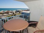 Dining and lounging space on private balcony overlooking beach and Gulf