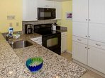 Kitchen with granite counters and black appliances