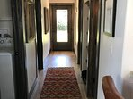 The hallway leads past the laundry room, bathroom, and 2 bedrooms to the back patio and hot tub.