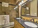 This spacious bathroom features a walk-in shower and double sinks.