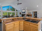 In the center of the kitchen is a wraparound island with a gas stove and plenty of room to prepare meals.