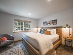 The guest bedroom has a king-size bed in a rustic frame and a comfy contemporary rocking chair.