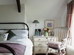 The Cottage master bedroom, with king-sized iron bed, en suite shower room & sea views