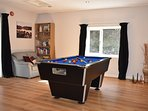 The games room with pool table and boardgames.