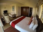 The second bedroom on the first floor has a TV and a wraparound balcony