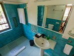 Washroom attached to the second bedroom on the first floor, done in blue tiles with free amenities