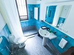Shower room attached to the ground floor bedroom done in blue tiles with free amenities