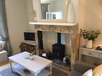 Cosy coastal cottage lounge with sandstone fireplace, log burning stove, smart tv with DVD player.