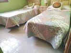 Dormitorio dos camas con ventilador techo y armario