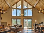 Tall windows frame peaceful Sierra views in this Groveland vacation rental cabin.
