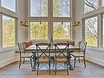 The eating nook contains a wood table with matching chairs and a built-in bench.