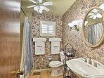 Flower-printed wallpaper fills the second bathroom.