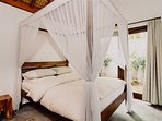 The beautiful mosquito net draped 4 poster teak bed  is very much the center  feature of the room.