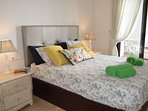 Dormitorio con cama doble y persianas motorizadas